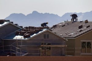Roofers work on new homes at a residential construction site